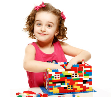 Young girl building a lego house